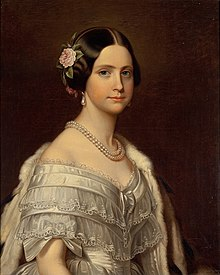 Half-length painted portrait of a young woman wearing a white satin ball gown trimmed with lace and bows, and also wearing an ermine stole thrown over one shoulder, a double strand of large pearls around her neck, pearl drop earrings, and a pink camellia arranged in the hair over her right ear.