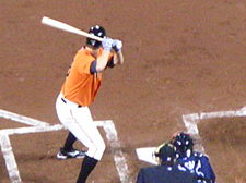 A man wearing an orange baseball uniform holding a baseball bat over his right shoulder