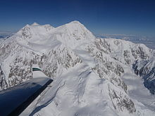 An aerial view of Mount McKinley. An airplane wing is visible in the lower-left corner.