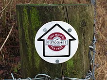 Wooden post with circular waymarker showing an arrow containing the logo of Butcombe Brewery