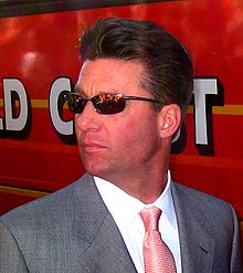 A man wearing sunglasses and a gray suit with a patterned red tie looking over his right shoulder
