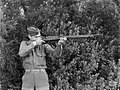 Military serviceman poses looking down the barrel of a rifle (AM 78397-1).jpg