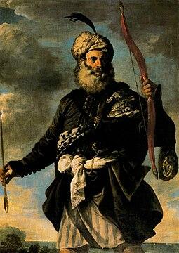 Homme vu de face en contre plongé tenant un arc