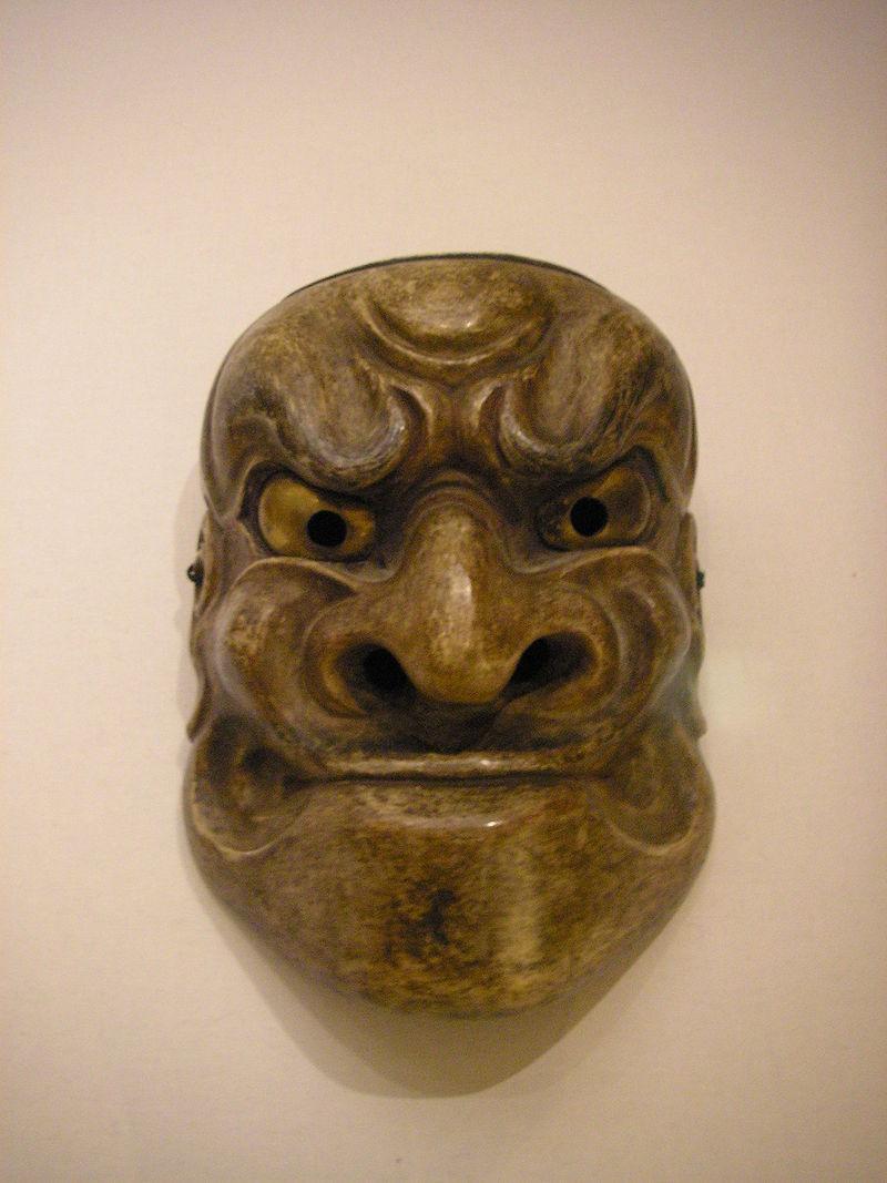 Masque large en bois, humanoïde, d'aspect inquiétant.