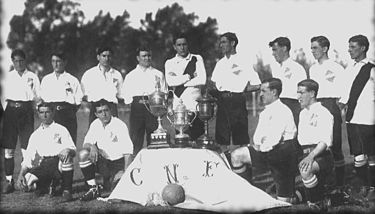 Nacional in 1915, posing with the three trophies won that year: Tie Cup, Primera Division and Copa de Honor Cousenier. Nacional urug 1915.jpg