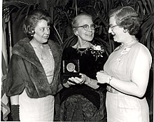 Three white women standing with an award, smiling