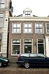foto van Huis met twee schilddaken, een brede lijstgevel en aan de straat twee dakkapellen met gebogen fronton en zijvoluten