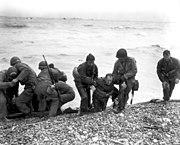 Survivors of a sunken troop transport wade ashore on Omaha Beach.