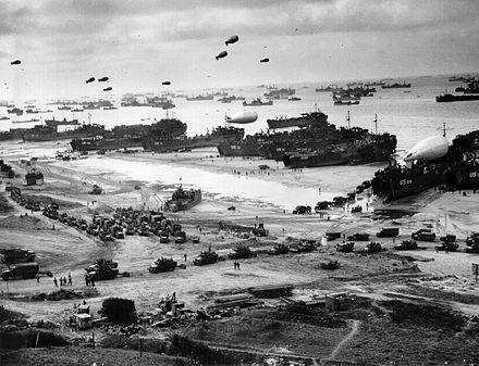 Landing ships putting cargo ashore on one of the invasion beaches during the Battle of Normandy. Note the barrage balloons. - Barrage balloon
