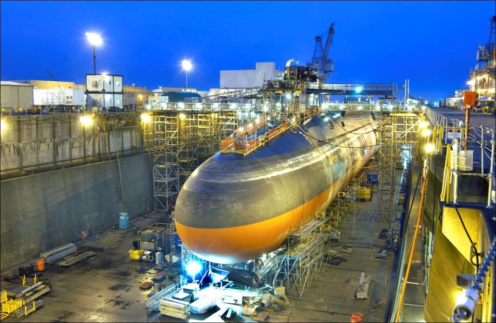 Black submarine with orange paint from cheatline down in drydock at nightfall