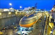 Black submarine with orange paint from cheatline down in drydock at nightfall.