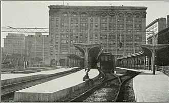 Tracks in a yard elevated above street level serve interurban lines at the Main Street Station, c. 1920 Pacific Electric Building and station.jpg