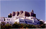 Fortress of dark stones on a hill above a town with white houses.