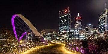 Le passage du pont, éclairée de lumières rasantes, de nuit. Sur le coté une arche violette jaillit dans le ciel. Au bout de la perspective des buildings qui se donnent des allures de gratte-ciel.