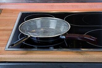 Splatter guard - A metal splatter guard on a frying pan.