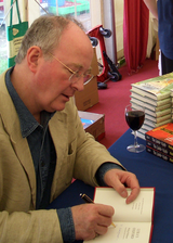 A balding man wearing rimless glasses is sitting at a table autographing books. He is wearing a sports coat. A glass of wine and a stack of books are on the table.