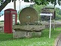 Phone box and millstone (29212322684).jpg
