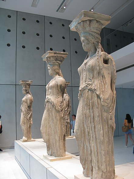 The Caryatides (Karuatides), or Maidens of Karyai, as displayed in the new Acropolis Museum. One of the female sculptures was taken away from the Erechteion by Lord Elgin and is kept in the British Museum. Porch of the Maidens (Caryatids) 2.jpg