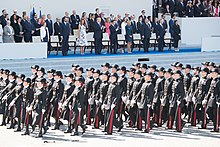 Photograph showing Presidents Macron and Trump and other dignitaries standing in the background reviewing French troops marching in the foreground at the 2017 Bastille Day celebrations in Paris, France