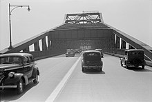 A grayscale photo of a four lane undivided road on a bridge