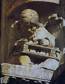 Medieval carving of a man with long hair and a long beard hunched over a musical instrument he is working on