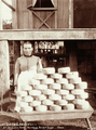 Queensland State Archives 2386 A woman with a stack of cheeses at Mrs Berganns Farm Teutoberg Blackall Range c 1899.png