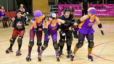 Two Wellington skaters (in purple) form a wall, limiting their opponents' movement, while their jammer (leftmost skater in purple) takes a hip whip to accelerate past the pack Roller Derby (22).jpg