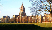 A wide shot of an old English school with a central tower, with a sports pitch in the foreground.