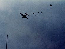 Four small parachutes can be seen coming out the back of a distant, silhouetted plane in flight. It is daytime, however the sky is dark and cloudy.