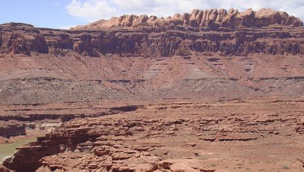 The Permian through Jurassic stratigraphy of the Colorado Plateau area of southeastern Utah that makes up much of the famous prominent rock formations in protected areas such as Capitol Reef National Park and Canyonlands National Park. From top to bottom: Rounded tan domes of the Navajo Sandstone, layered red Kayenta Formation, cliff-forming, vertically jointed, red Wingate Sandstone, slope-forming, purplish Chinle Formation, layered, lighter-red Moenkopi Formation, and white, layered Cutler Formation sandstone. Picture from Glen Canyon National Recreation Area, Utah. SEUtahStrat.JPG