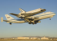 A modified 747 on take-off carrying piggyback the Orbiter of the Space Shuttle. Small fins are added to the 747's horizontal stabilizer for improved performance.