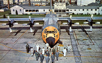 Sewart Air Force Base - Postcard with personnel posed around new C-130 Hercules by Base Operations building.  In the foreground are crew members such as pilot, co-pilot, navigator, flight engineer, scanner and loadmaster. Supporting personnel such as fire fighter, cook, nurse, weather observer, etc. form the balance of the troop carrier pyramid.
