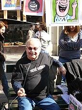Siné sur le stand de Siné Hebdo lors de la manifestation du 19 mars