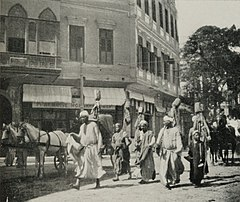 "Standard-Bearers in a Procession with an ""Arabeah"" (Cairo Cab) Behind. (1911) - TIMEA.jpg"