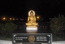 Gold-coloured, seated Buddha statue on a pedestal
