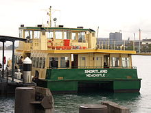 "Rear of a ferry boat with jetty to its left. Boat has ""Shortland"" and ""Newcastle"" on the back"