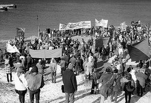 """En samling af mennesker, omkring 150, med skilte, som beder om at """"stoppe broen"""" og lade """"finanshajerne"""" svømme."""