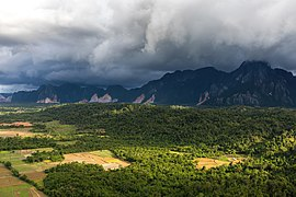 Sunlight and stormy sky over the mountains and paddy fields in Vang Vieng, Laos.jpg