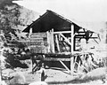 Historic photograph of Sutter's Mill in Coloma in 1850. It is a largely open-walled wooden building set on stits among sparsely vegetated mountains.