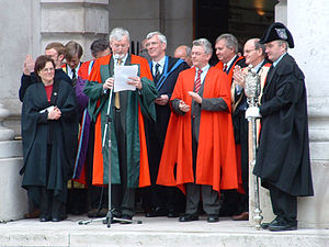 Academic dress of the University of Dublin - The announcement of new Fellows and Scholars of the College on Trinity Monday – Doctors in Philosophy and Science can be seen, with a Master of Arts in the centre, a Bachelor to the left and a mace-bearer to the right, as well as officials wearing academic dress of other institutions