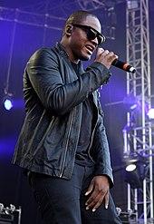 A picture of a man wearing sunglasses and singing with a microphone