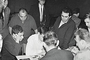 Tigran Petrosian - Petrosian (standing on right, with jacket) at the 1961 European Chess Team Championship. Seated, facing right, is Mikhail Tal, then world champion.