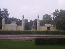 Trees surrounding a white stone obelisk shaped monument, inside a white walled compound, with hedges in the foreground
