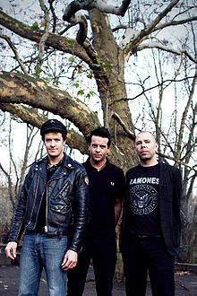Three men stand in front of a bare tree. All are shown in three-quarter body shot and facing forward. Man at left is tallest, he has dark hair and wears a dark cap, a dark leather jacket which is unzipped, and blue jeans. He holds his arms along his sides. Middle man is slightly shorter, with dark clothes and his arms behind his back. He is partly behind and obscured by first man. Third man is shortest, his head hair is very short and sparse and his hands are behind his back. He wears a dark jacket and pants, with a dark tee shirt that features 'Ramones' printed across it with a logo below and names encircling it.