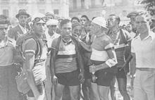 Photographie en noir et blanc montrant un groupe de coureurs à l'arrivée d'une étape.