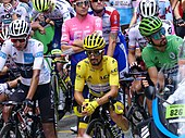 Three cyclists waiting with their bicycles in front of several others or more, with each of the three wearing white, yellow and green jerseys