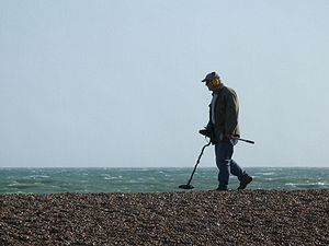 Man with metal detector on the Brighton Beach.