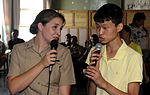 U.S. Navy Information Systems Technician Seaman Apprentice Jenna Welsh, left, assigned to U.S. 7th Fleet command ship USS Blue Ridge (LCC 19), sings karaoke with Nam Jae Kyung during a community service project 100824-N-XG305-288.jpg