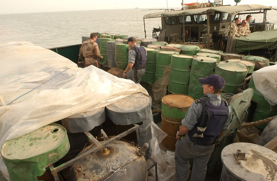 US Navy 030321-N-4655M-028 Coalition Navy Explosive Ordnance Disposal (EOD) team members inspect camouflaged mines hidden inside oil barrels on the deck of an Iraqi shipping barge