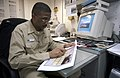US Navy 030412-N-9964S-505 Chief Photographer's Mate Wayne Edwards proofreads a rough draft of pages from USS Harry S. Truman (CVN 75) cruise book.jpg